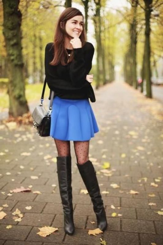 Dark colored mini skirt paired with a black long sleeved shirt and knee length boots